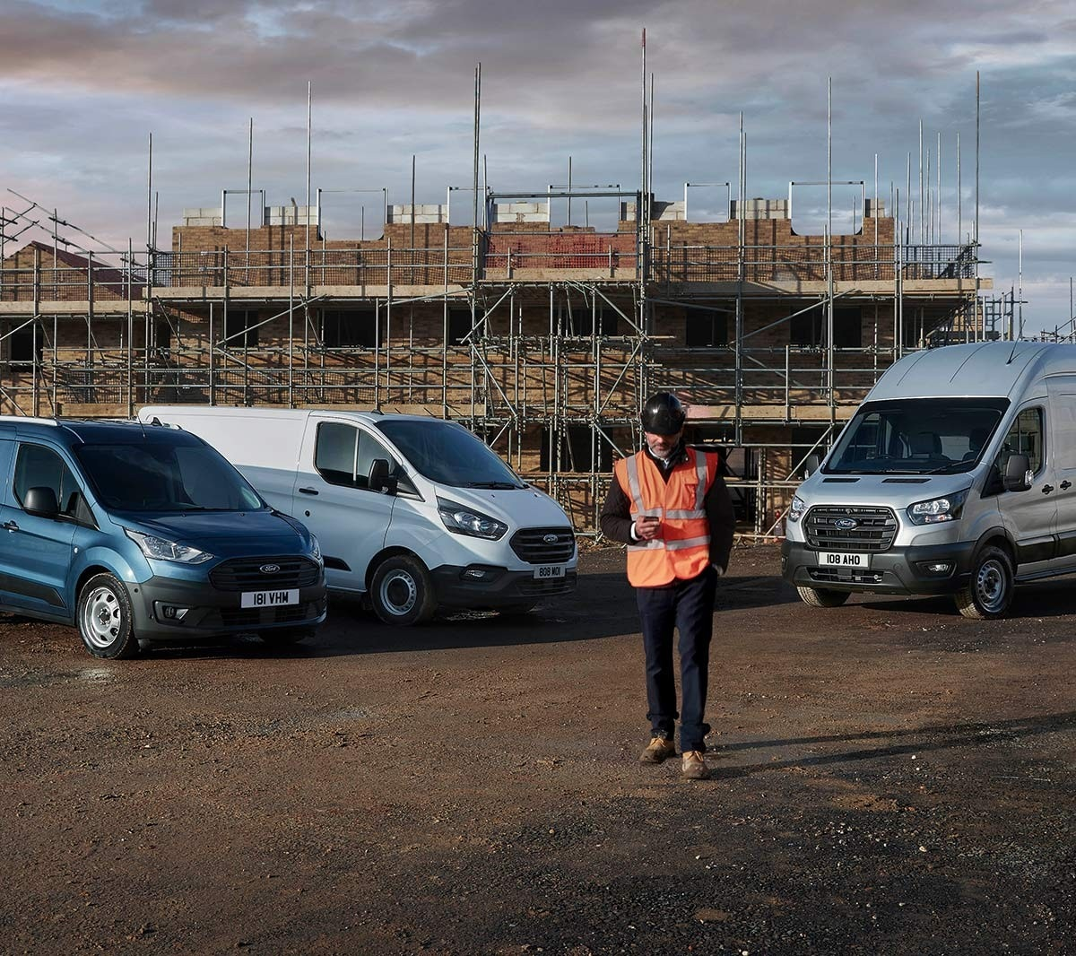 Building site with man in high viz jacket and various Ford cars