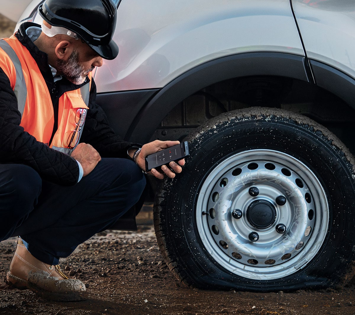 Service person in high viz jacket checking flat tyre